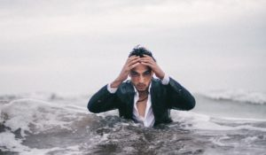 Verzweifelt aussehender Mann steht in Meereswellen; Visualisierung zu Burnout